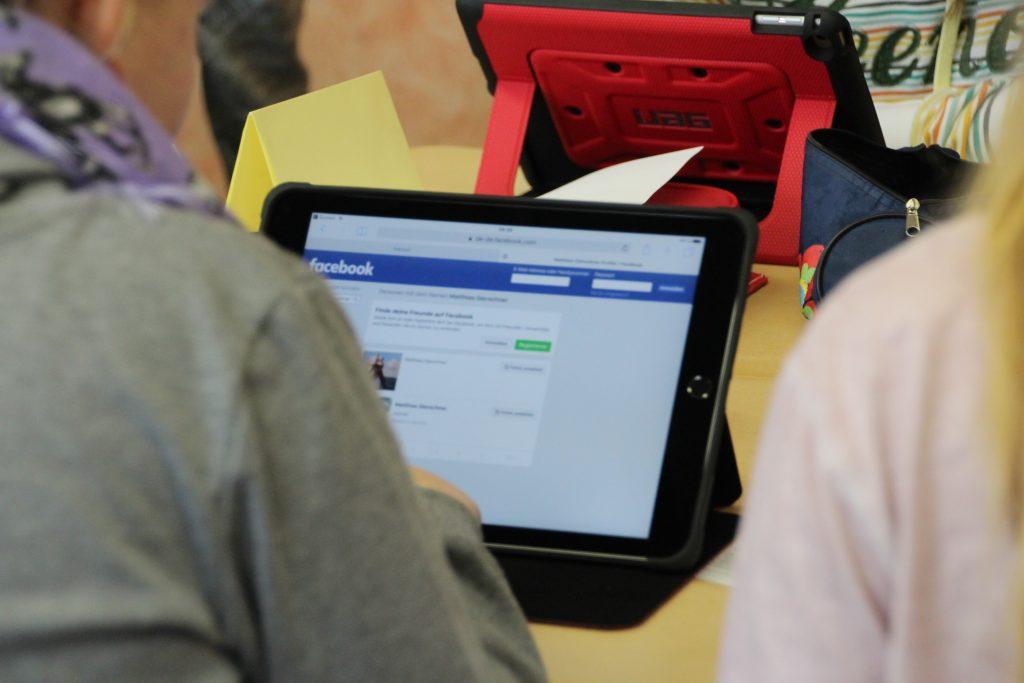 Grundschüler sitzen vor Tablets und beschäftigen sich mit sozialen Netzwerken.